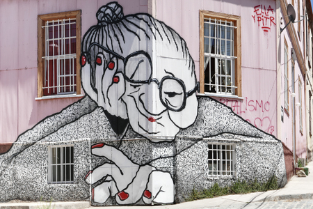 VALPARAISO, CHILE - OCTOBER 29, 2014: Graffiti of an old woman sprayed on a building facade in Valparaiso, Chile. Valparaiso Historic center is a UNESCO world heritage site Éditoriale