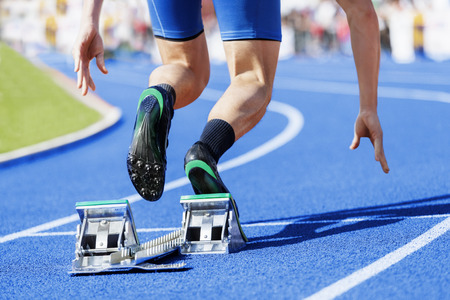 racing track: Track and field runner starts out of the blocks. Stock Photo
