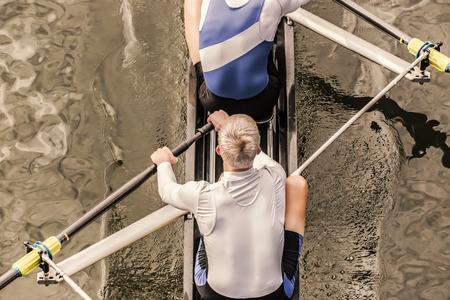 Bovenaanzicht van twee atletische concurrentie roeier, die een beroerte hun peddel door het water. Stockfoto