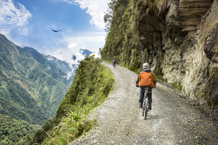 Bike adventure travel photo. Bike tourists  ride on the road of death  downhill track  in Bolivia. In the background sky circles a condor over the scene.
