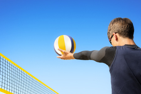 concentrates: Beach volleyball player concentrates to pitch the ball over the net