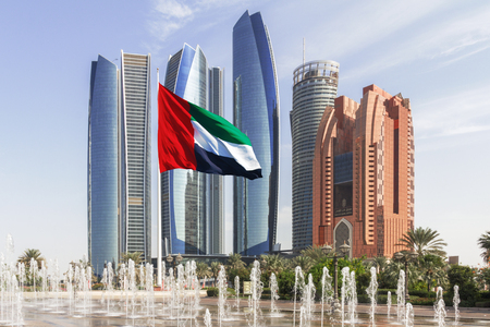ABU DHABI, UAE - OCTOBER 23, 2015: Etihad tower ensemble in Abu Dhabi with fountains and flag in the foreground