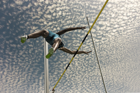 Male pole vaulter jumps  over the yellow black striped bar