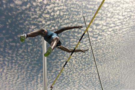 Maschio saltatore con l'asta salta sopra la barra gialla a strisce nero Archivio Fotografico - 54943263