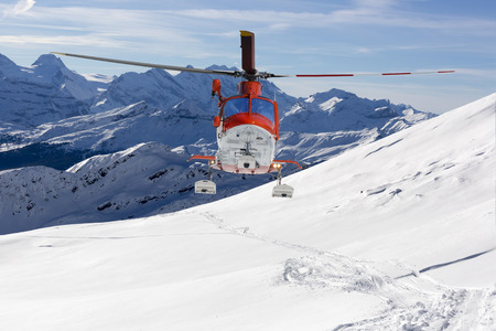 Rescue helicopter lands in snow capped mountains