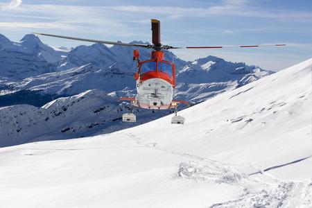 superficie: tierras de rescate en helicóptero en las montañas nevadas