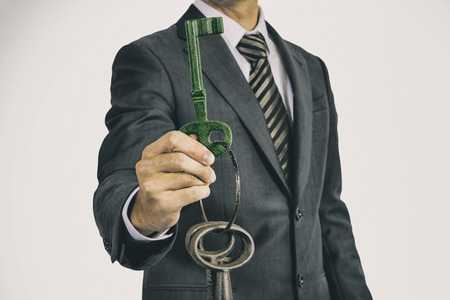 analogue: Man in business suit  holds a bunch of oversized historic keys in front of his body. The analogue film effect underlines the age of the keys.  The held and shown key has a green overlay. The photography can be used to illustrate environment themes.