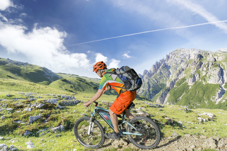 E bike traveler with backpack rides a mountain trail Archivio Fotografico