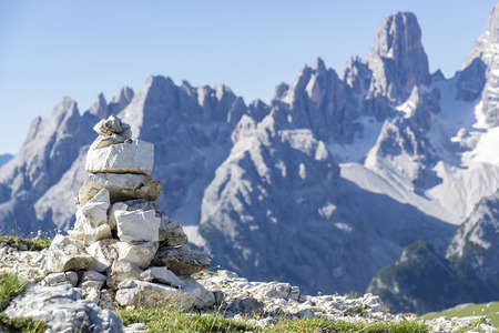 stapled: Stacked rough rocks with the typical mountains of the dolomites in the background