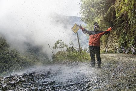 Bike adventure travel photo. Bike tourist  on the road of death enjoys the waterfall. Stock Photo