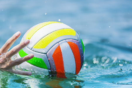 beachball: A hand of a swimmer reaches for a beachball in the water