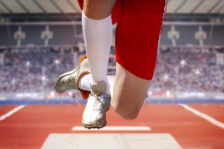 スタジアムでの長いジャンパーは、サンド ボックスにジャンプします。背景は、輝く懐中電灯で十分に占められた観客テラスを示しています。 写真素材
