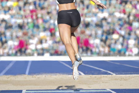 jumpers: Female long jumpers jump into the sand box. In the background there can be seen fully occupied ranks with spectators. Stock Photo