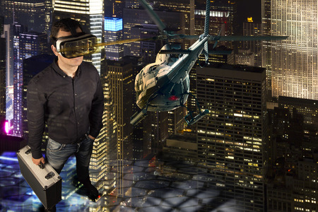 A person wears virtual reality glasses and  holds a metal suitcase in his hand. He stands in a virtual reality environment of New York at night. A helicopter flies through the scene. Reklamní fotografie