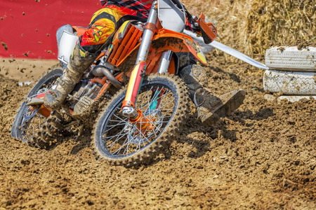 Action packed scene of a moto cross rider in a race, who plows through deep mud.