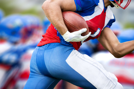 touchdown: Side view of american football player who runs with the ball to make a touchdown. In the blurred background there can be seen his run protecting team.