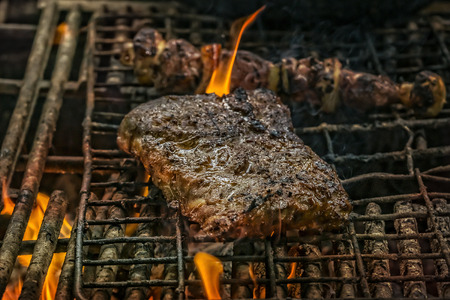 meat grill: South african barbecue outdoor kitchen with spareribs and meat skewer on the grill.