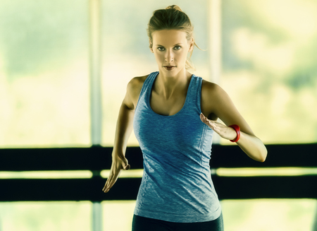 Energetic runnning workout of a young woman in a glass framed corridor. She wears a fitness tracker on her left arm. Stock Photo