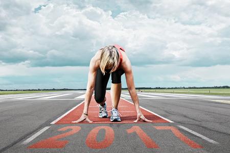 Weiblicher Läufer wartet auf die 2017 Start auf einer Landebahn des Flughafens. Im Vordergrund perspektivische Ansicht des Datums 2017.