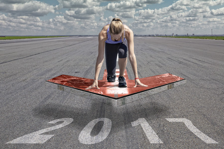 start position: Female runner kneels in start position on a red floating arrow platform, which is placed above an airport runway surface. The runway surface shows the date of the year 2017. Stock Photo
