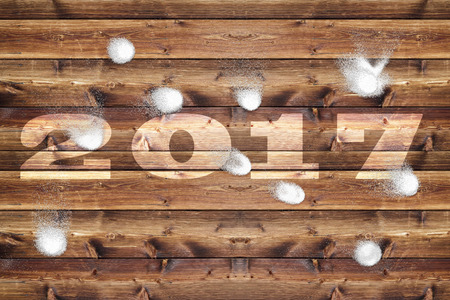 bombardment: Wooden board with bleached out 2017 letters, which is bombarded with snowballs.