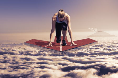 Female runner kneels in start position on a floating red arrow platform, which hovers at late sunset over the clouds  Stock Photo