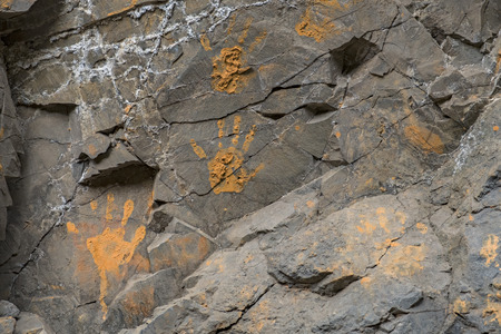 handprints: Muddy orange hand prints on a cracked stone wall Stock Photo