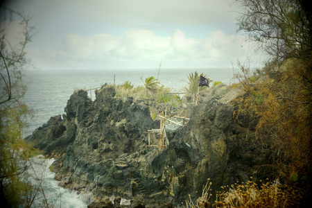 outlaws: Look-out site with pirate banner on a land tongue in the north of la Palma. Toy camera effect underlines the mood of the picture.