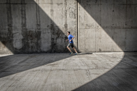 arcades: Side view of male runner with blue shirt and smart watch, who runs under concrete arcades.