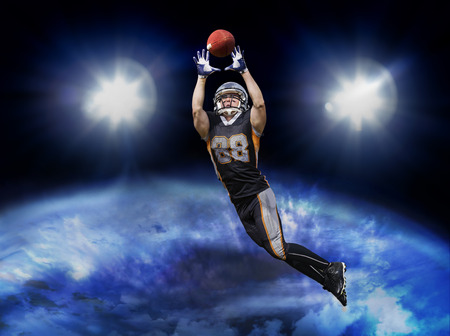 American football player jumps into the orbit to catch the ball. The shirt shows the lucky number 88. Stock Photo
