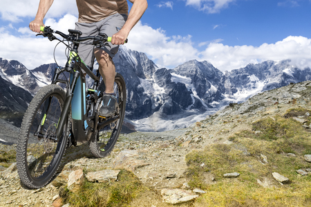 Single mountain bike rider on E bike rides up a steep mountain trail. Stock Photo