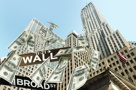 Hundred dollar bills money falling down the buildings of the Wall street. The road signs wall street corner broad street show the location.