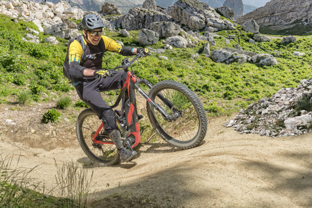 E bike rider in middle age enjoys the power of the e bike on a steep uphill trail. Banque d'images