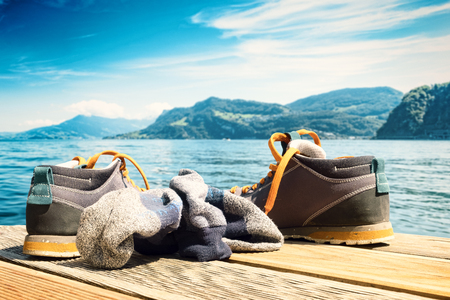 Trendy hiking boots and socks of the owner lying on a wooden lake platform. The background shows the picturesque lake lucerne.
