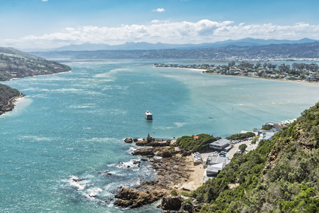 Lagoon of Knysna with its aquamarine colored water. A tourist boat is cruising in the beautiful lagoon. Stock Photo