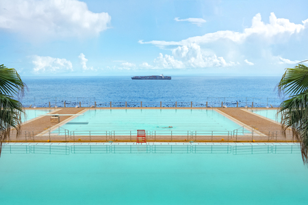 Outdoor swimming pool with turquoise water, surrounded of palms and an ocean. A single swimmer swims his lanes and a container ship crosses the background. Stock Photo