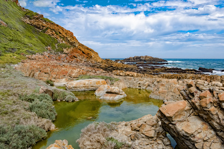 Tremendous Robbberg nature reserve coastline at Plettenberg bay South Africa. The foreground shows a picturesque natural basin between the red rocks. Stock Photo
