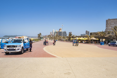 DURBAN, SOUTH AFRICA - NOVEMBER =2, 2017: People are walking on the bay of plenty promenade. The foreground shows a police car with officers.