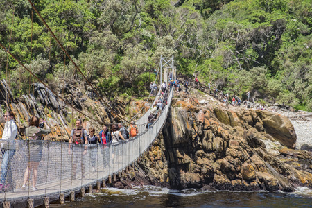 TSITSIKAMMA, SOUTH AFRICA - NOVEMBER 08, 2017: Tourists are walking on the storms river mouth suspension bridge. It is one of the landmarks in this region