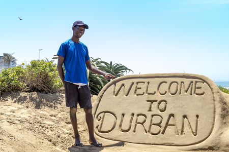 DURBAN, SOUTH AFRICA- NOVEMBER 02, 2017: Unknown sand sculpture builder at bay Plenty in Durban stands beside his artwork and points to it.