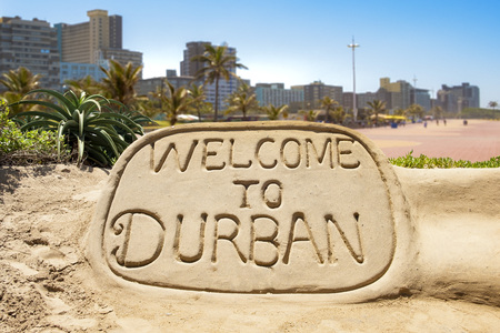 Welcome to Durban sand sculpture with skyline of Durban bay of plenty in the background Stock Photo