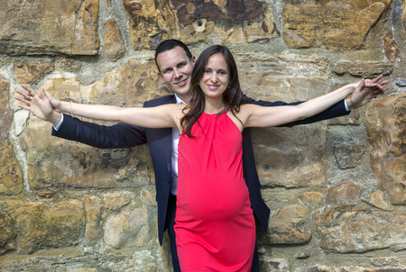 Stylish pregnant couple in the thirties standing behind each other with spreaded arms.