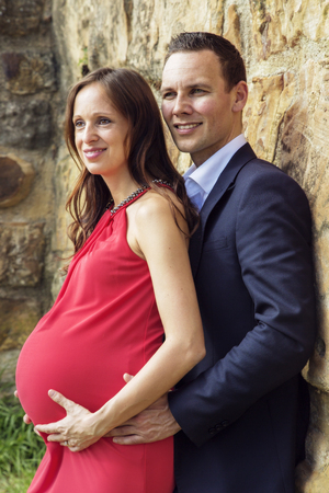 Stylish couple in the thirties with pregnant woman standing on medieval wall. They look into the distance.