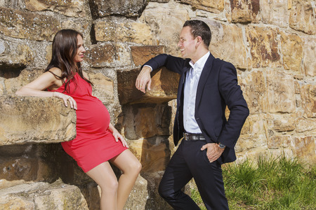 Stylish couple in the thirties with pregnant woman standing on medieval wall and talk to each other.