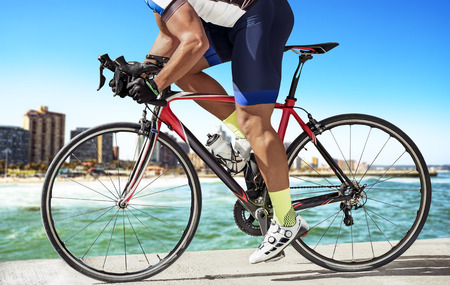 Side view photo of a race biker, biking on a pier in front of an urban skyline.He pushes out of th saddle to speed up his bike.
