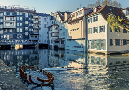The photo shows the old quarter Small Venice in Esslingen with the Neckar river and an old wreck in the foreground.