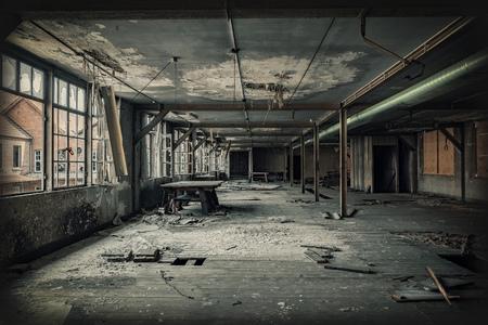 Desolate hall of a factory ruin. Light is shining through the broken windows