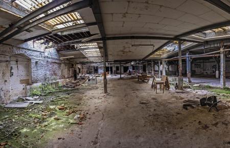 Desolate hall of a factory ruin. Light rays are shining through the broken windows