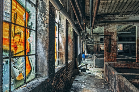 Perspective view of industrial ruin interior with its sprayed windows Stock Photo