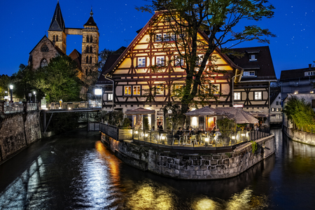 ESSLINGEN, GERMANY - APRIL 17, 2018: Night scene of the old quarter of Esslingen with the old building Alte Zimmerei surrounded by the Neckar river in the foreground.